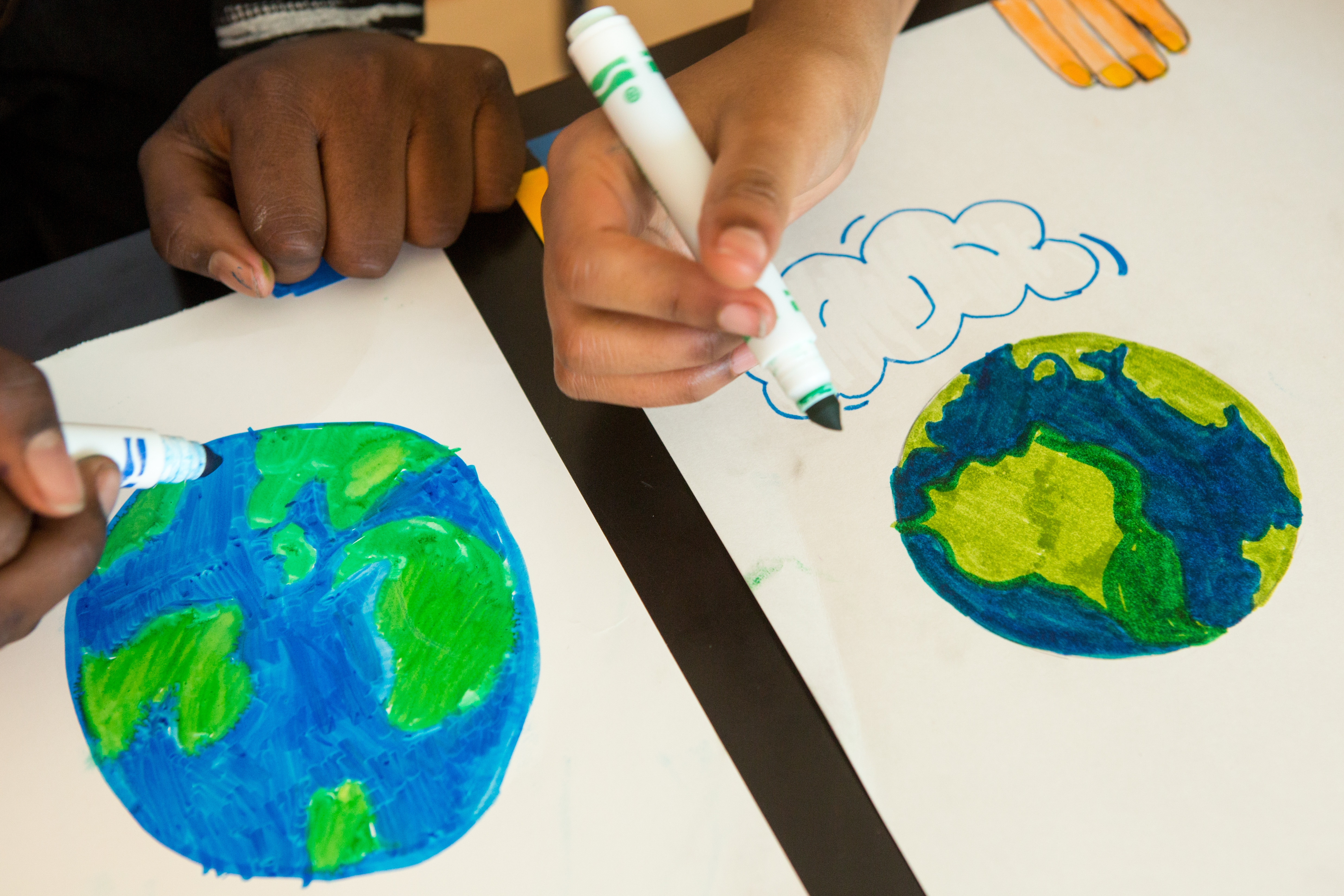 Two student hands drawing pictures of the Earth