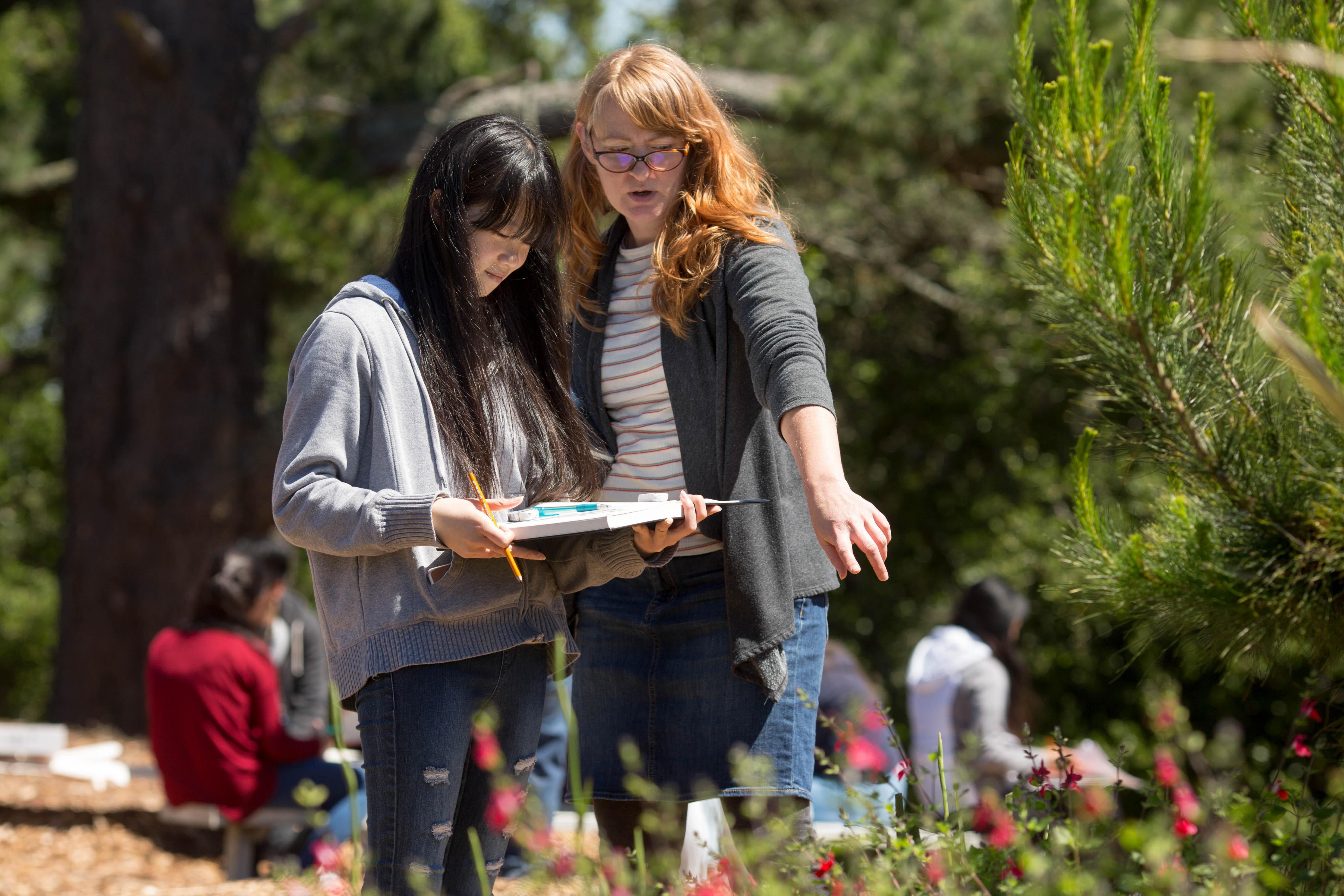 Teacher pointing to garden standing with student