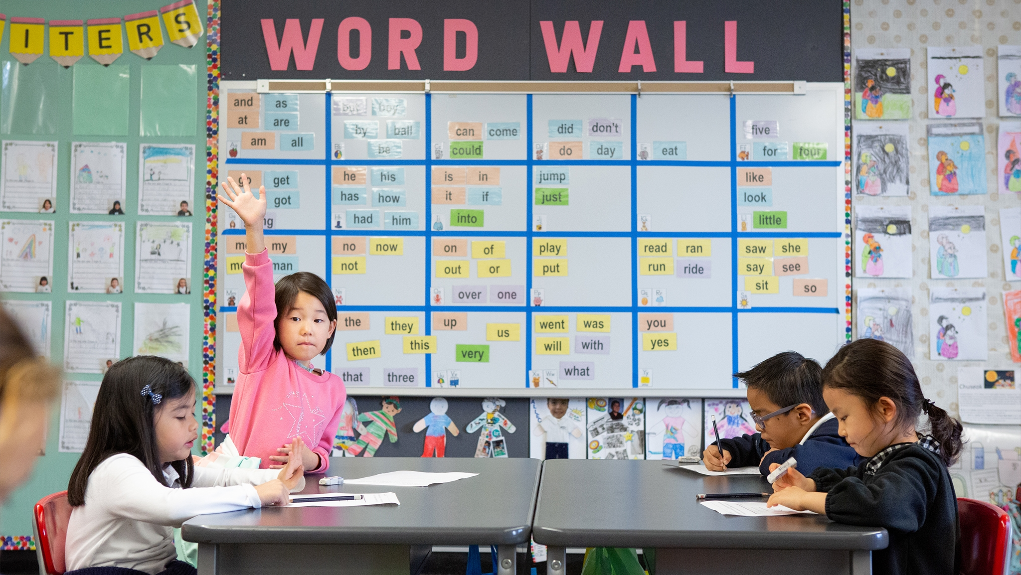 A kindergarten student raises her hand in a dual-language immersion class.