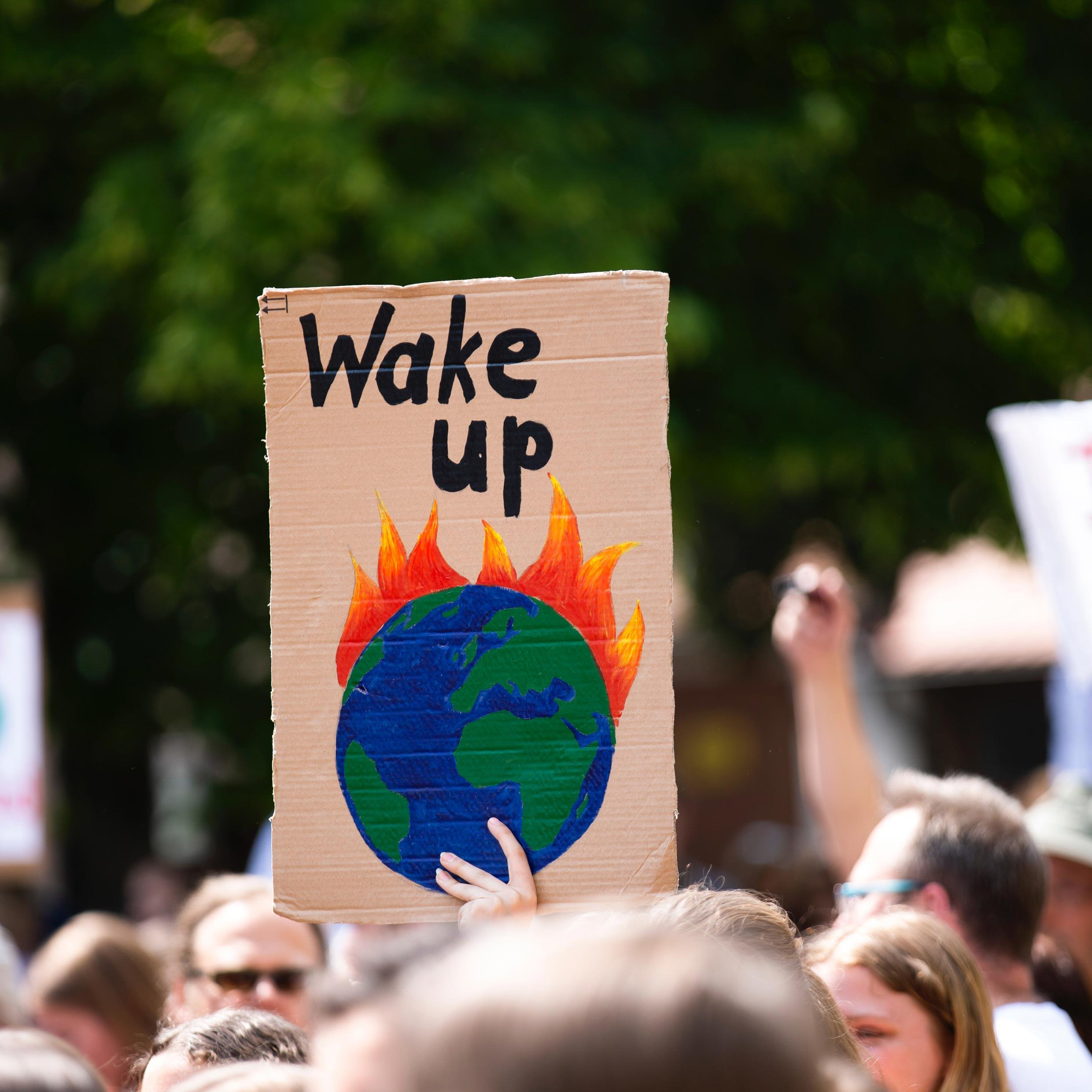 Protester holding sign with earth on fire saying wake up